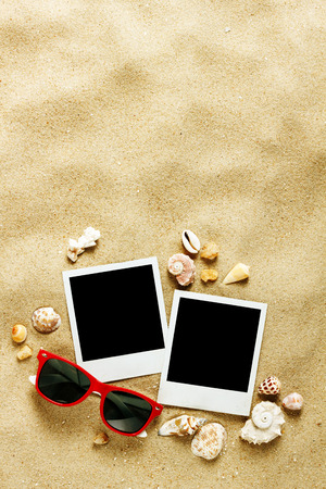 Instant photo frames on the beach with seashells around  photo