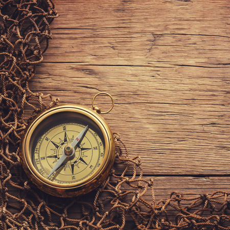 traverse: Antique brass compass over wooden background