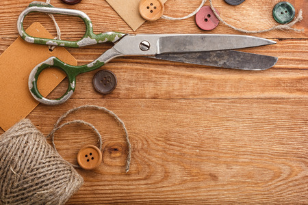 Old scissors and buttons on the wooden table photo