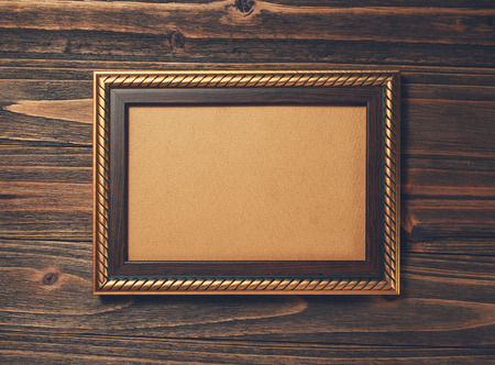 ornamentations: ancient style golden photo image frame on wood background Stock Photo