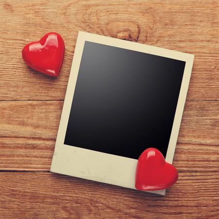 Marco de fotos y pequeños corazones rojos sobre fondo de madera vieja, ruta interior