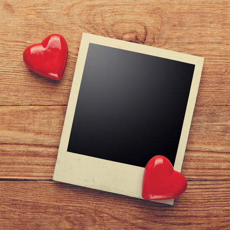 photo paper: Photo frame and small red hearts on old wood background, path inside