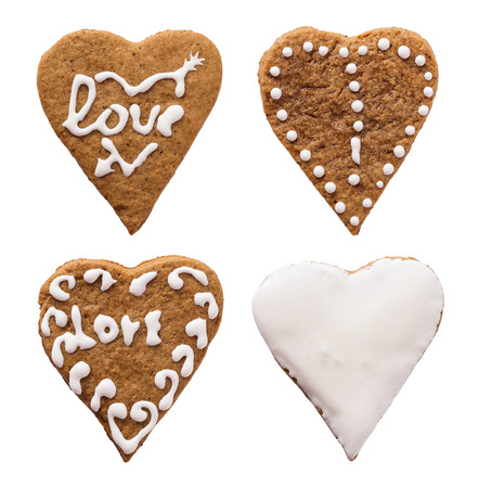 Four individual heart-shaped cookies for Valentines Day over white photo