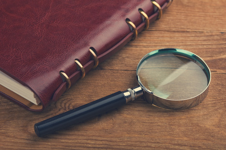 Notebook with a magnifier on wood table photo
