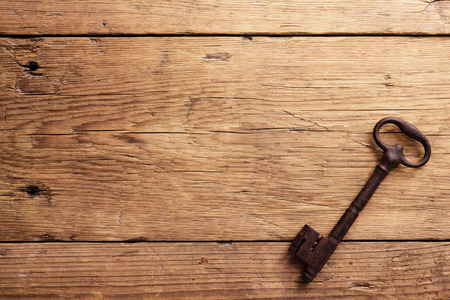 golden key: Old key on a wooden background