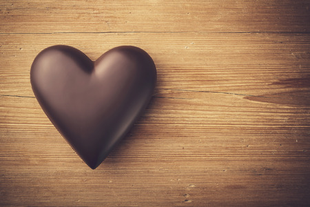 Chocolate heart on wooden background Banco de Imagens