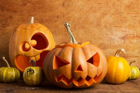 carved pumpkin: pumpkins on wooden background