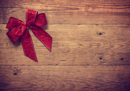 Decorative red ribbon and bow over wooden background