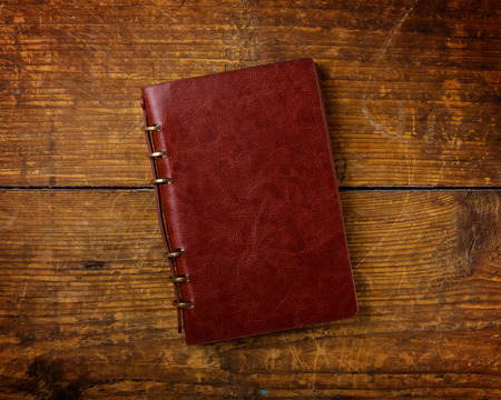 Notebook on wood background Imagens