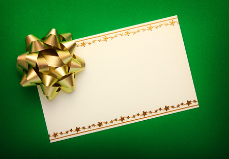 gold bow: Greeting card on green paper with gold bow