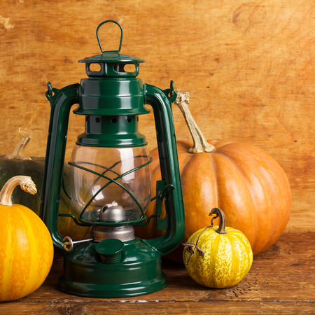 lantern and colorful pumpkins on wooden table