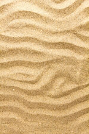 Closeup of sand pattern of a beach in the summer day. Nature background.