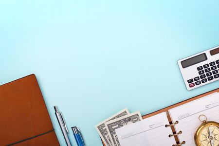 Business background. Calculator, notebook, pen, compass and dollars on blank paper background.
