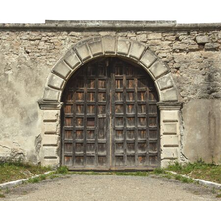 Medieval gate of an old castle surrounded by a stone wall. Architectural object, vintage door.