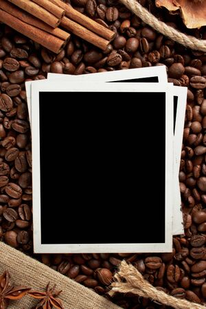 Old photo frames against the backdrop of coffee beans and cinnamon