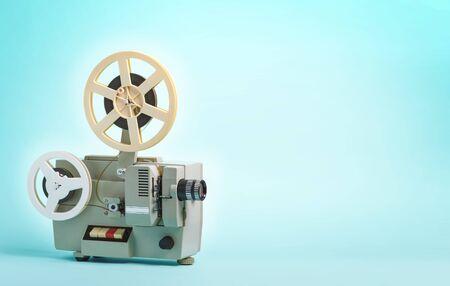Old cinema projector on blue background 免版税图像