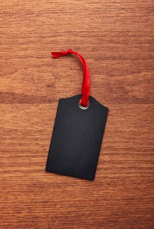 Black tag with red ribbon on wooden background. Empty place for text. 免版税图像