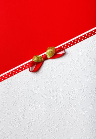 Christmas gift wrap ribbon and bow, red paper background, white paper background, copy space