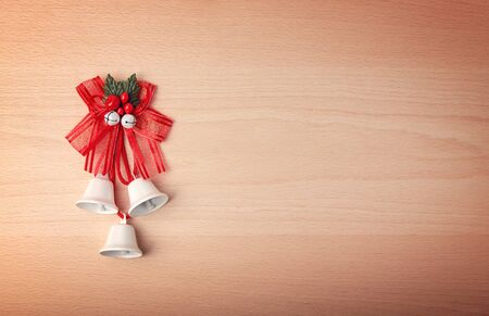 Jingle bells, bows and Christmas decorations on a light wooden background. Place for text. 免版税图像