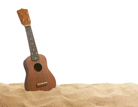 Guitar ukulele on sand beach white background. Summer beach with copy space. Travel concept.