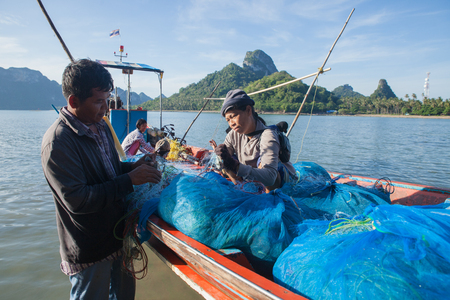 surat: SURAT THANI, THAILAND - MAY 30: Unidentify fishermen working on th boat on May 30,2015 in Donsak pier, Surat Thani, Thailand. Theyre unfasten crabs from the net.