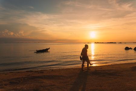 Tourists walk along the beach at sunset in koh Phangan, Thailand.