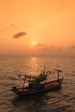 Fishing boat on the sea in sunset scene. Stock Photo