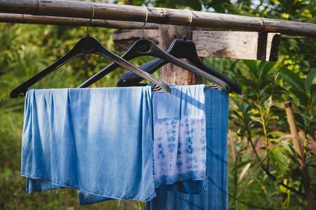 Indigo fabric hanging near the green garden.