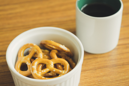 Mini pretzels in the bowl and black coffee on wooden background.
