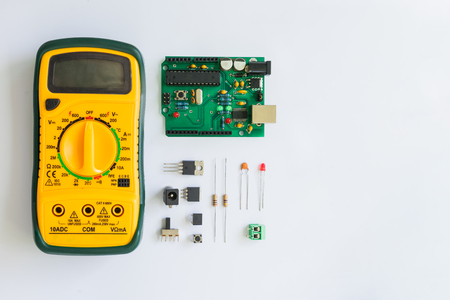 Top view of Multimeter and electronics component such as resistor, ICs, capacitor, switch, relay and connector on white background. Banco de Imagens