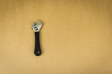 Wrench tool on brown background.