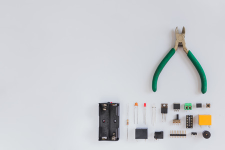 Top view of pliers and electronics component such as resistor, ICs, capacitor, switch, and connector on white background.