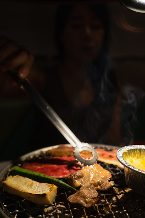 Asian woman with beef barbecue on the grill. Japanese and Korean Food concept.