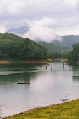 Fisherman and small fishing boat and floating in Bang Lang reservoir in the rain. Stock Photo