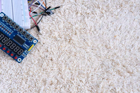 Electronic circuits with wires lie on a table on a light beige carpet.