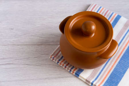 A small clay pot stands on a light wooden table and a light striped towel.