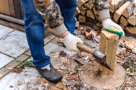 A man in gloves and blue jeans cuts and cleans birch firewood with an ax with a wooden handle, with which a fireplace, stove or a fire will be heated.