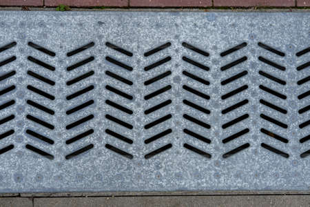 Close-up wide metal grating for rainwater drainage, mounted between concrete and paving stones.
