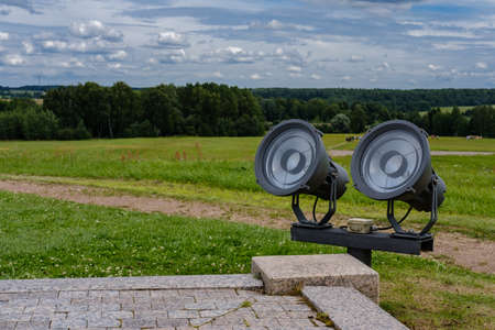 Two round spotlights in the park are directed upwards against the background of a field with green grass, forest and sky with clouds.