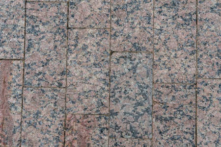 A walkway of old rectangular granite tiles, lying tightly together in a chaotic order.