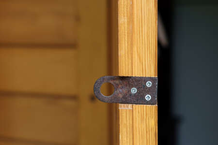 An old rusty padlock lug is bolted to the wooden door of the country house.