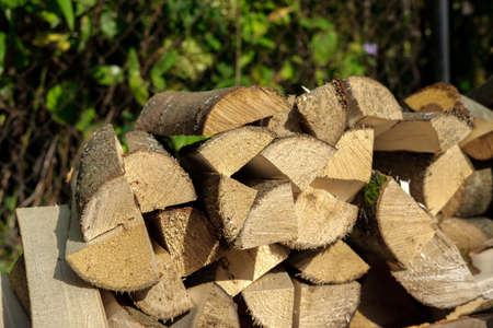 Finely chopped firewood for a stove, fireplace or barbecue, stacked randomly in a small pile and illuminated by the sun's rays.