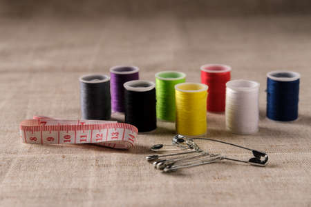 The multicolored threads on the sewing bobbins lie on the thick beige fabric next to the sewing tape and pins.