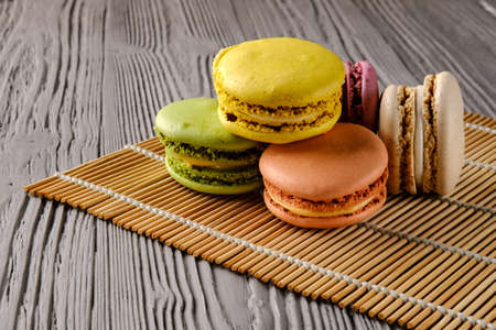 Macaroni cookies, of different colors, lie side by side on a bamboo roll mat on a textured gray wooden table.