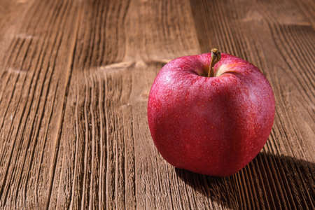 One red apple lies on a textured brown wooden table and casts a hard shadow, close-up.