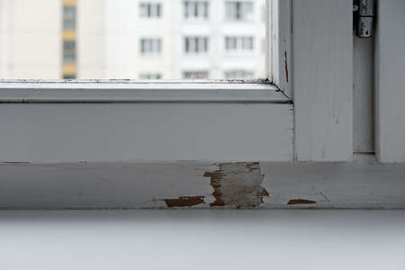 Old white window frame with glass with scratches, stains and places of peeling and cracked paint. Stock fotó