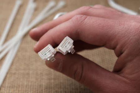 A wire with two RJ-45 connectors for connecting the Internet in a man's hand against a light beige fabric background, on which there are cable ties.