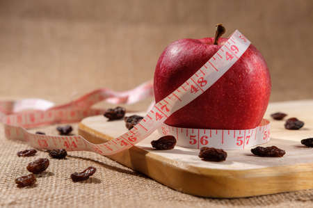 One red dietary apple for weight loss lies on a wooden board on the table, a centimeter wrapped in a measuring line, and raisins are randomly scattered around. Stock fotó