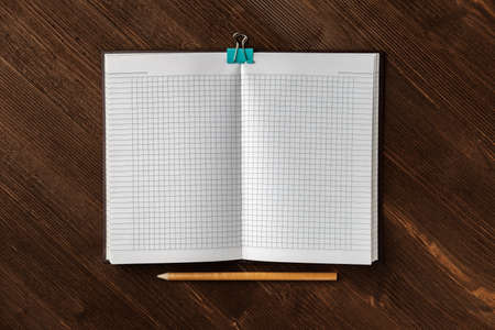 A notebook with squared paper for notes and a light-colored pencil lie on a textured dark wooden table. Stock fotó