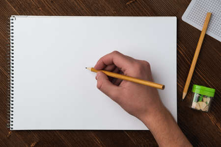 A young man holds a pencil in his hand over a sketchbook with white sheets, which lies on a textured dark wooden table next to a green sharpener. Stock fotó
